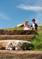 A pair of plush rabbits in the foreground and a boy and girl in the distance