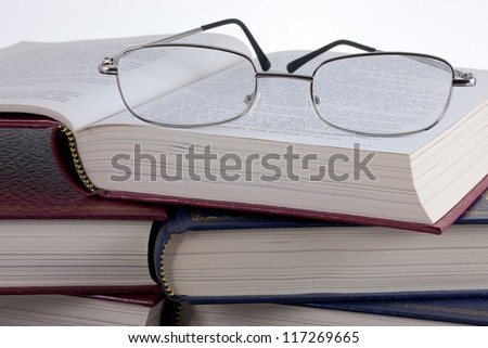A pair of reading glasses on a pile of old, leather bound books