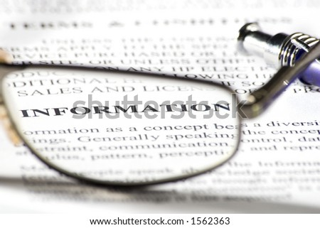 A pair of reading glasses on paper and the word 'information' in focus