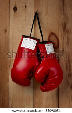 A pair of red boxing gloves hangs from a nail