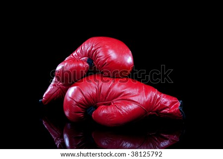A pair of red leather boxing gloves on a black background with copy space
