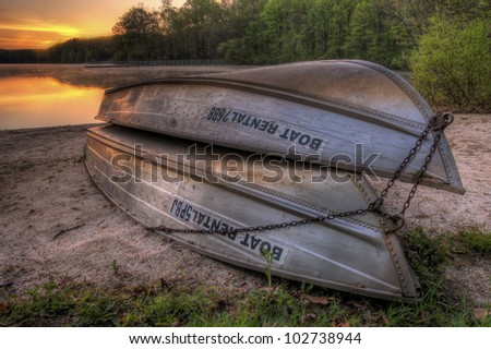 A pair of rental boats by a beautiful lake at sunrise.