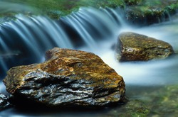 A pair of river rocks with a small waterfall flowing behind them