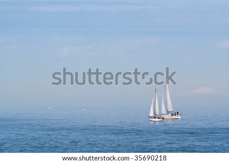 A pair of sailboats in the sea. Calm weather