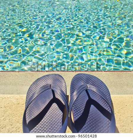 A pair of sandals by the swimming pool in summer