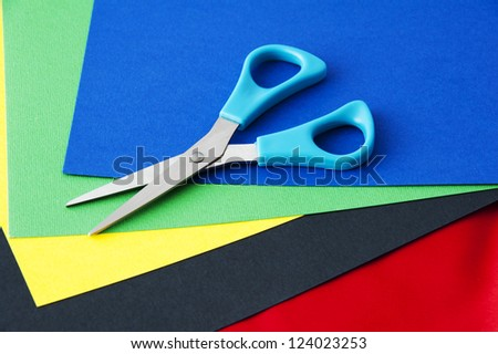 a pair of scissors on colored paper