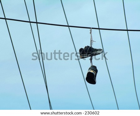 A pair  of shoes hanging from a powerline.
