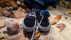 a pair of shoes stored on the beach sand