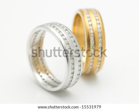 A pair of silver and gold diamond rings