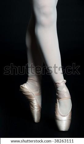 A pair of slender ballerina legs on tip toe against black background
