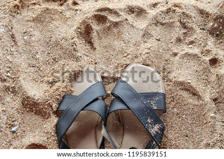 A pair of slippers are on the beach partial covered with sand