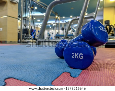 A pair of small blue dumbbells of 2 kilograms placed on rubber gym floor with different gym interior equipment around for weight loss and strength training
