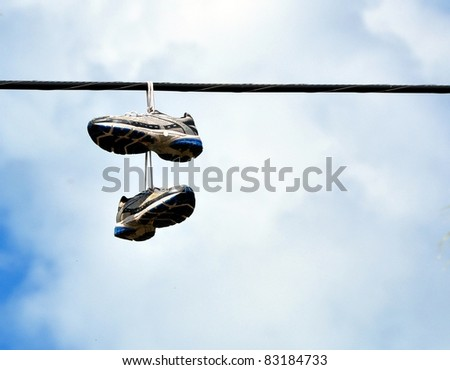 A Pair Of Sneakers Hanging From A Power Line