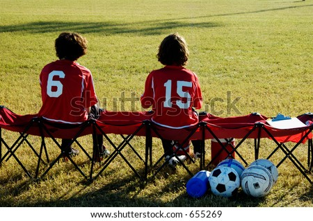 A pair of soccer players watch from the bench.