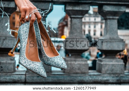 A pair of sparkly sequin clad stiletto shoes and fairy lights held by hand