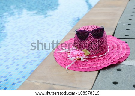 A pair of sunglasses and summer hat resting on the side of pool.