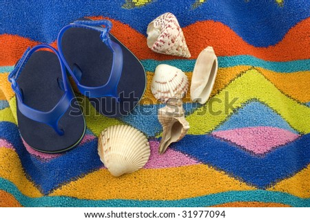 A pair of tiny blue infant sandals on a colorful beach towel with a collection of seashells, horizontal with copy space