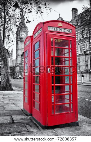 A pair of traditional red phone booths in London with the Big Ben in a desaturated background