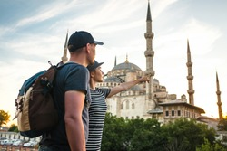 A pair of travelers near the world-famous Blue Mosque in Istanbul, Turkey. The girl shows direction.