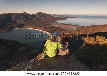 A pair of traveller couple watching sunrise at the peak of Mount Amos with Wineglass Bay at the background, Freycinet National Park, Coles Bay, Tasmania, Australia Photo stock ©