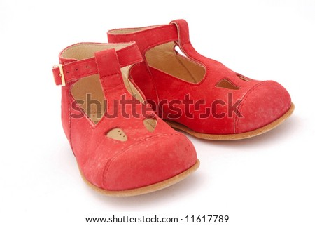 A pair of two little dirty red Italian leather shoes for kids isolated on white background