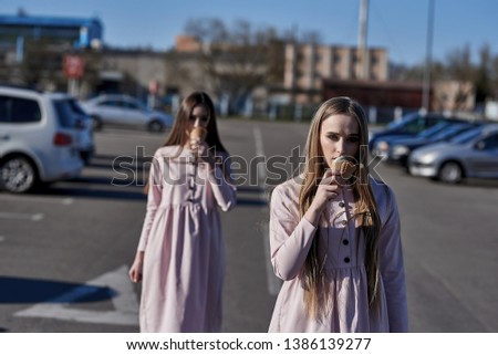 A pair of two pretty sexy pretty women or girls who eat ice cream on the street, pink dresses #1386139277