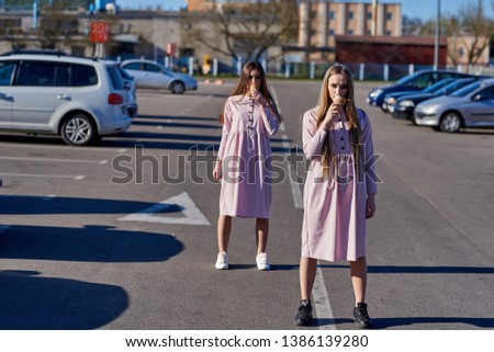 A pair of two pretty sexy pretty women or girls who eat ice cream on the street, pink dresses #1386139280