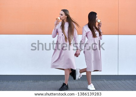 A pair of two pretty sexy pretty women or girls who eat ice cream on the street, pink dresses #1386139283
