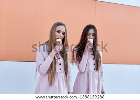 A pair of two pretty sexy pretty women or girls who eat ice cream on the street, pink dresses #1386139286