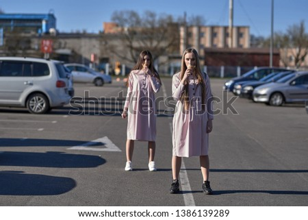 A pair of two pretty sexy pretty women or girls who eat ice cream on the street, pink dresses