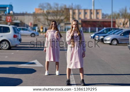 A pair of two pretty sexy pretty women or girls who eat ice cream on the street, pink dresses #1386139295