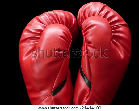 A pair of two red boxing gloves with black stripe close up on black background.