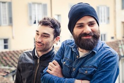 A pair of two young men take a break from work in the terrace of a building. One has a beard, hat and a shirt, the other a leather jacket