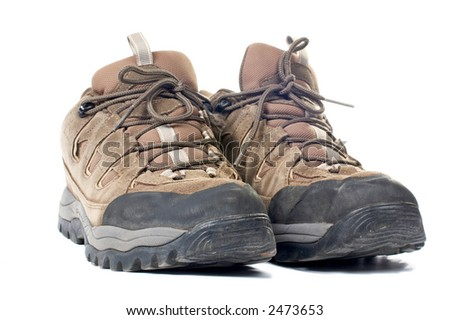 A pair of used hiking boots with shadow over a white background