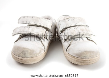 a pair of used kid trainers isolated on white