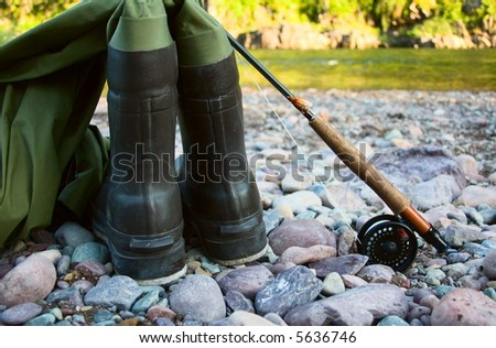 A pair of waders sit along a river bed with a fishing rod and reel, ready to be used for flyfishing.