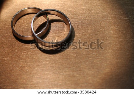 A pair of wedding bands against a gold-colored background.