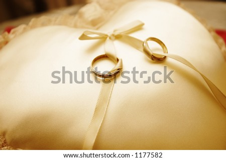 a pair of wedding rings on a golden pillow.
