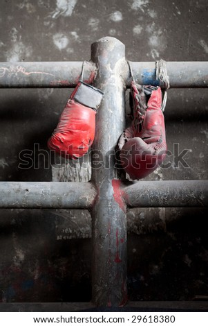 A pair of well used, dusty Muay Thai boxing gloves hanging against a grungy boxing ring