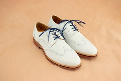 A pair of white nubuck bucks with a bright blue laces on. This fashionable footwear is a classic for mens leather shoes.