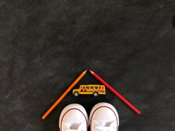 a pair of white shoes are seen under a yellow toy school bus with two coloring pencils forming a triangle, flat lay on a blackboard, copy space
