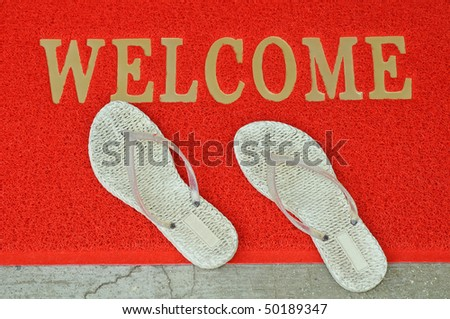 A Pair Of White Slippers On A Welcome Mat