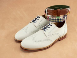 A pair of white wingtip bucks with a matching gingham colorful belt. Mens fashion accessories.