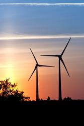 A pair of Wind turbine farm over sunset