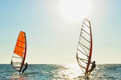 A pair of windsurfers in the sea on a sunny day.