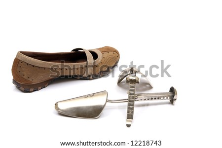 A pair of womens brown leather sandals against a white background with shoe stretcher used sizing shoes.