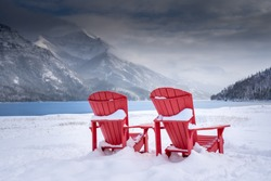 A pair of wooden chairs overlooking Waterton Lakes National Park Canada during the winter with a glacier lake