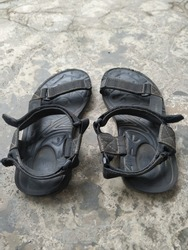 A pair of worn mountain sandals in a dull black color