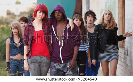 A pair of young punk teens pose together as their friends stay in the background.