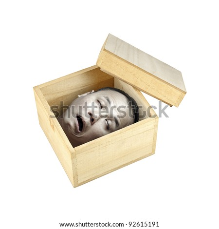 A pale preserved decapitated human head in an open timber box with its lid on the side, isolated against white for Halloween concept.